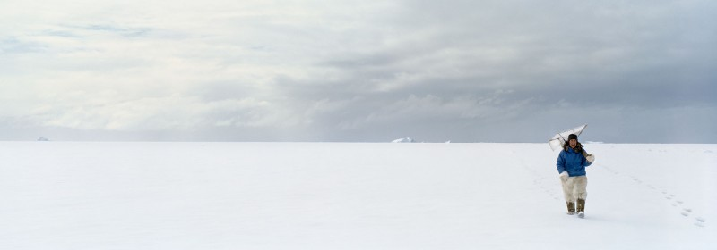 "Unartoq, 27.5"" x 79"", a hunter returns from the ice carrying his seal blind"